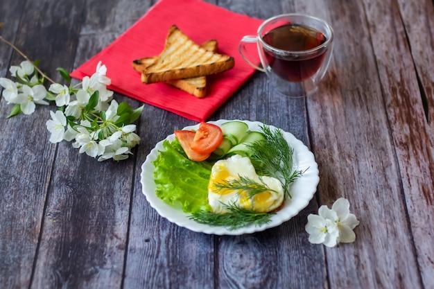Gebakken eieren met sla, komkommer en tomatenplakken op houten achtergrond
