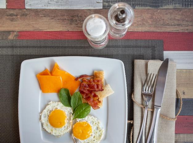 Gebakken eieren met spek en groenten op een bord op donkere achtergrond