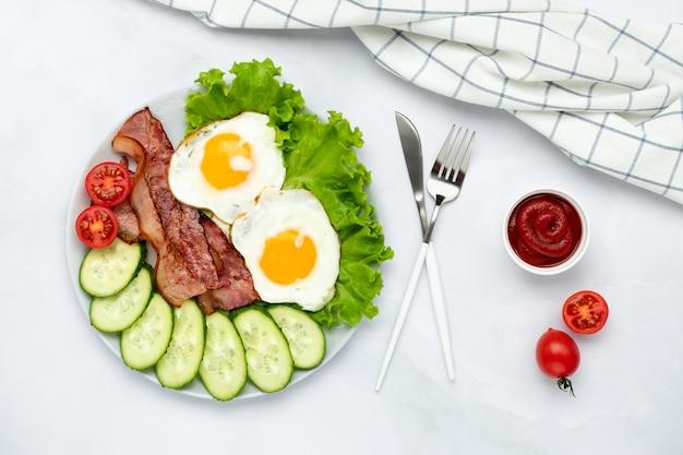 Gebakken eieren met spek en groenten op een grijze tafel, voedsel achtergrond in de ochtend. verse komkommers en tomaten. ontbijtconcept. bovenaanzicht. platliggende compositie.