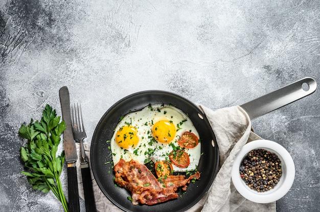 Gebakken eieren met spek in een pan. keto-dieet. keto ontbijt. low carb dieet concept. hoog-vetgehalte dieet. grijze achtergrond. bovenaanzicht. ruimte voor tekst