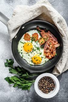 Gebakken eieren met spek in een pan. keto-dieet. keto ontbijt. low carb dieet concept. hoog-vetgehalte dieet. grijze achtergrond. bovenaanzicht