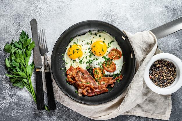 Gebakken eieren met spek in een pan. keto dieet.