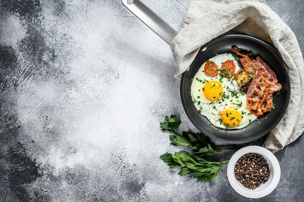 Gebakken eieren met spek in een pan.
