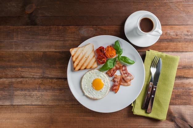 Gebakken eieren met spek op het ontbijt op houten rustieke planken, voedsel achtergrond