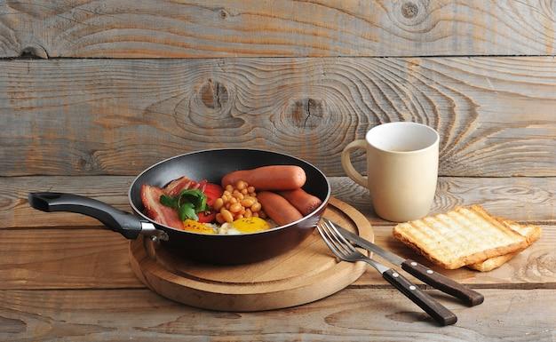 Gebakken eieren met spek, tomaten, bonen, champignons en worstjes in een koekepan en toast en koffie