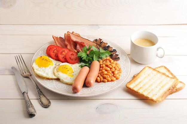 Gebakken eieren met spek, tomaten, bonen, champignons en worstjes in een schotel en toast en koffie