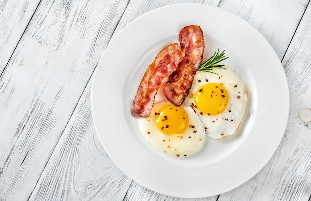 Gebakken eieren met spekreepjes op de witte plaat