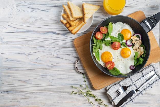 Gebakken eieren met tomaten, champignons en spinazieblaadjes in een koekenpan