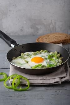 Gebakken eieren met verse peper op grijs
