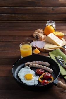 Gebakken eieren met worst en groenten op pan. ontbijt met oranje juise en croissant op houten rustieke planken, voedsel achtergrond.