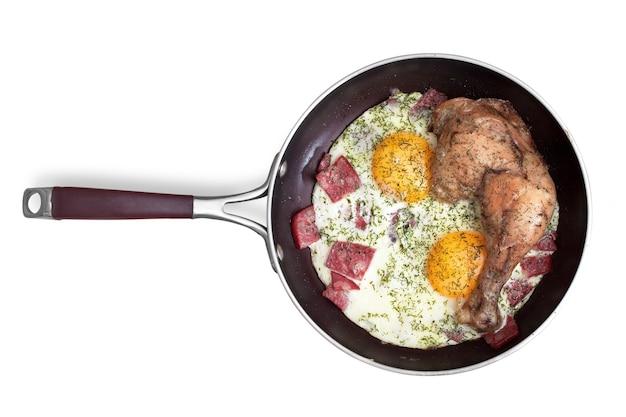 Gebakken eieren met worst en kippenpoot op een koekenpan. is geïsoleerd op een witte achtergrond
