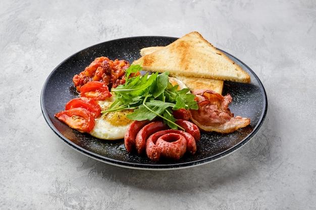 Gebakken eieren met worst, spek, tomaten en bonen op een bord met toast