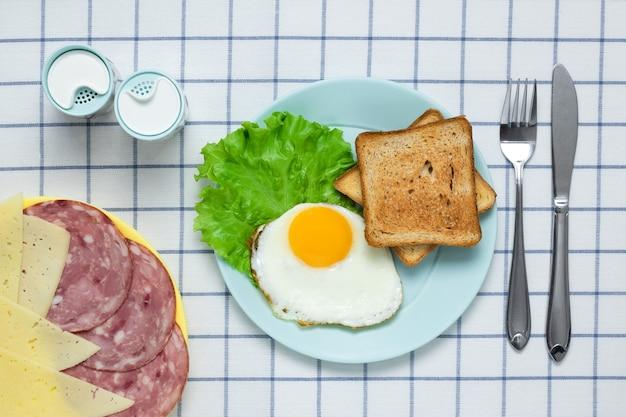 Gebakken eieren met worst, toast en kaas op een geruit tafelkleed