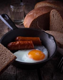 Gebakken eieren met worstjes in een pan. selectieve aandacht