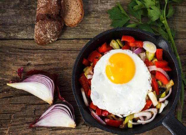 Gebakken eieren op groenten in een koekenpan op een houten tafel, met uien, brood en peterselie