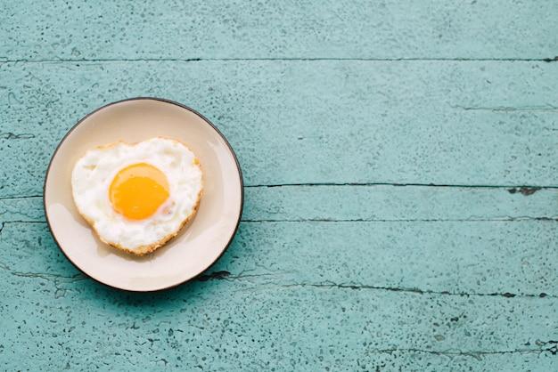 Gebakken eieren, toast, koffie, ontbijt set geplaatst op een blauwe houten tafel