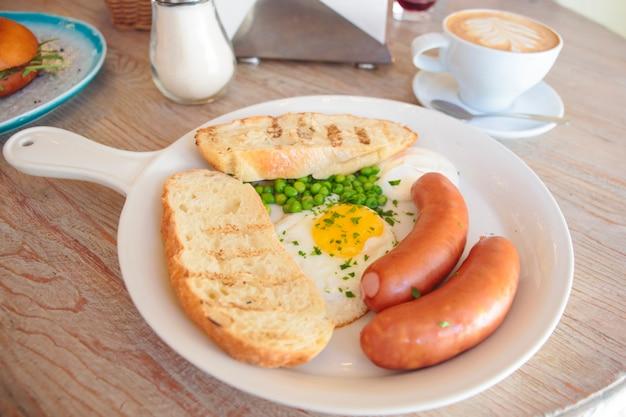 Gebakken eieren twee worstjes toast in een witte pan