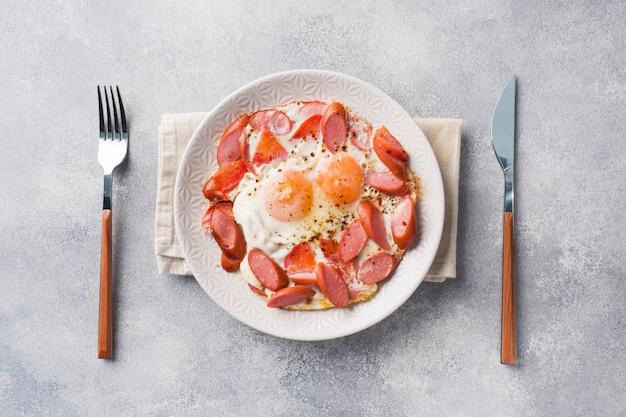 Gebakken eieren worstjes en tomaten op een bord op de tafel.
