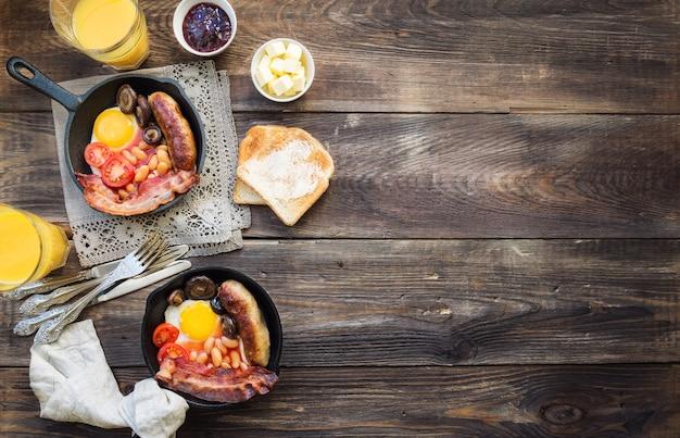 Gebakken eieren worstjes spek bonen en champignons in ijzeren koekenpan op rustieke houten achtergrond
