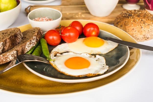 Gebakken eiomelet met brood, tomaat en erwten op plaat
