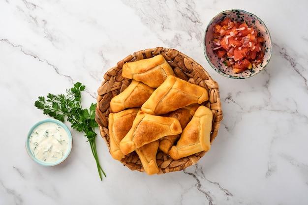 Gebakken empanadas met koriander, vlees, ei, tomaat en chilisaus op witte achtergrond. latijns-amerikaanse en chileense onafhankelijkheidsdag concept.