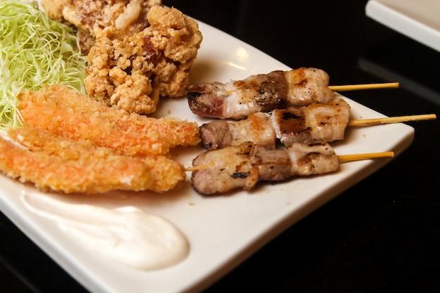 Gebakken en geroosterde stukken vlees en gesneden kool geserveerd op een witte plaat