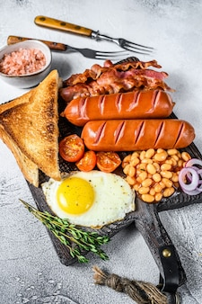 Gebakken engels ontbijt met gebakken eieren, worstjes, spek, bonen en toast op een houten snijplank. bovenaanzicht.