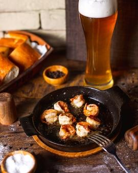 Gebakken garnalen geserveerd met glas bier