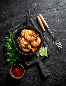 Gebakken garnalen in een koekenpan op een snijplank met saus, peterselie en schijfjes limoen. op zwarte rustieke ondergrond