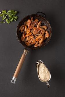 Gebakken garnalen in een pan met koriander