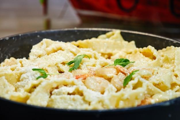 Gebakken garnalen met italiaanse pasta, parmezaanse kaas en kruiden in een pan.