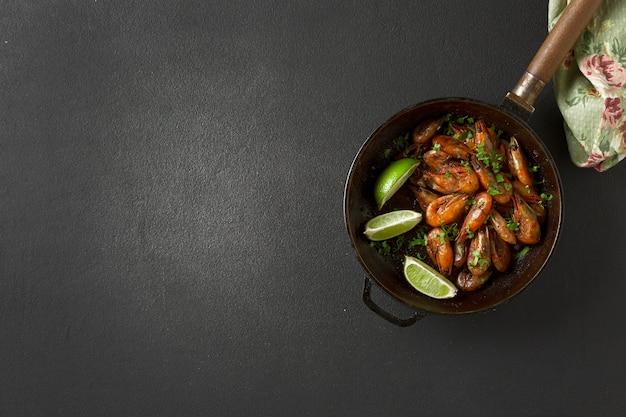 Gebakken garnalen met koriander en limoen in een koekenpan. bovenaanzicht. bier snack