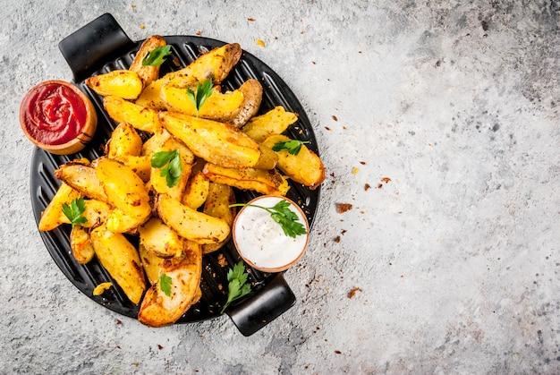 Gebakken gebakken aardappelen met knoflook, kruiden, rode en witte sauzen