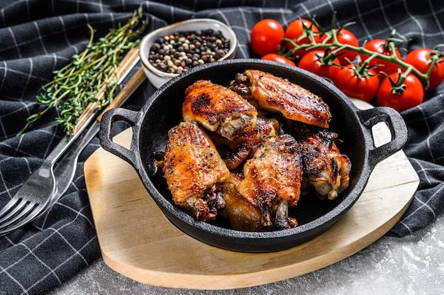 Gebakken geglazuurde kippenvleugels in een pan.