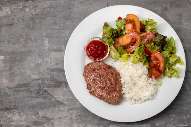 Gebakken gehakt met tomatensaus en gekookte rijst op schotel