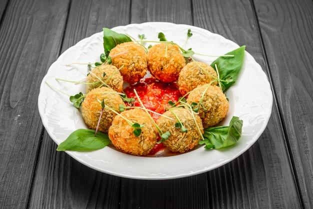 Gebakken gehaktballen met groenten en saus op plaat