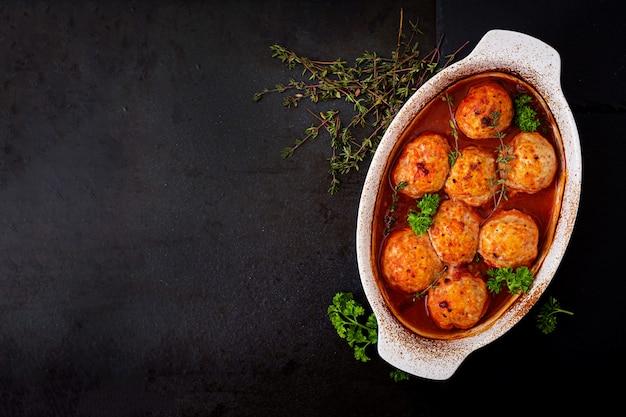Gebakken gehaktballetjes van kipfilet in tomatensaus.