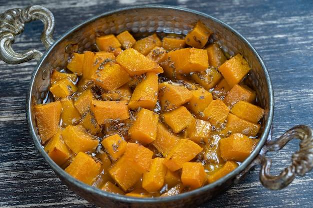 Gebakken gele pompoen met honing, anijs, olijfolie en kruiden op een bord op de houten tafel. vegetarisch eten. detailopname