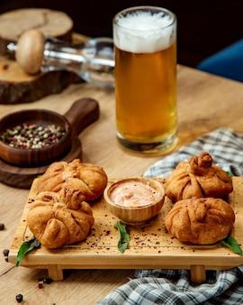 Gebakken georgische khinkali met saus op een houten dienblad