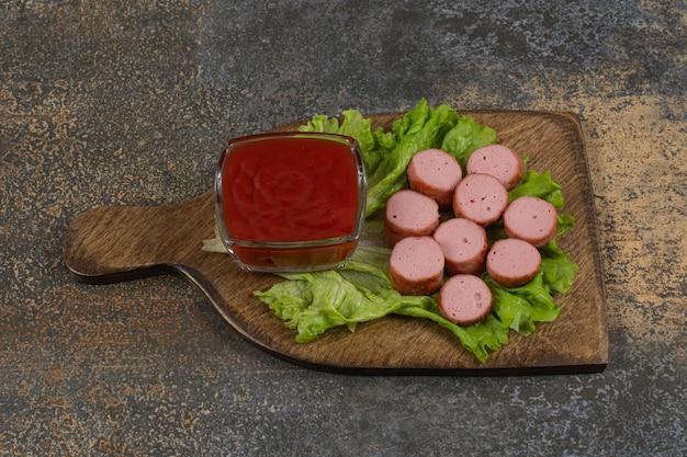 Gebakken gesneden worstjes en ketchup op een houten bord.