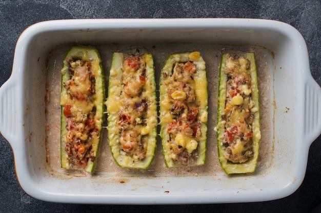 Gebakken gevulde courgetteboten met fijngehakte kippenpaddestoelen en groenten met kaas op een bakplaat. bovenaanzicht copyspace