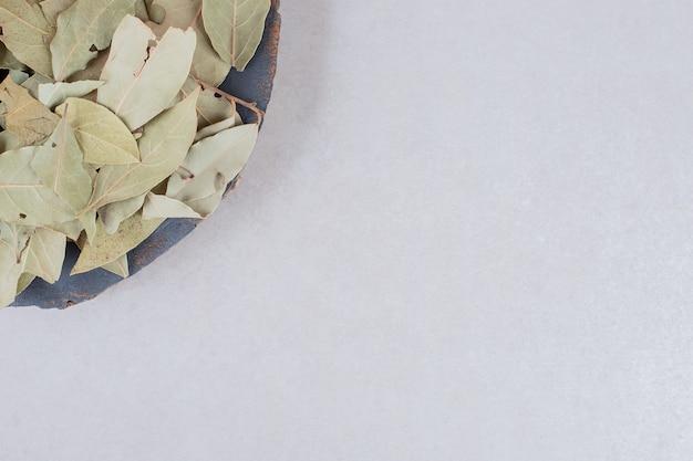 Gebakken groene laurierblaadjes op een houten rustieke schotel.