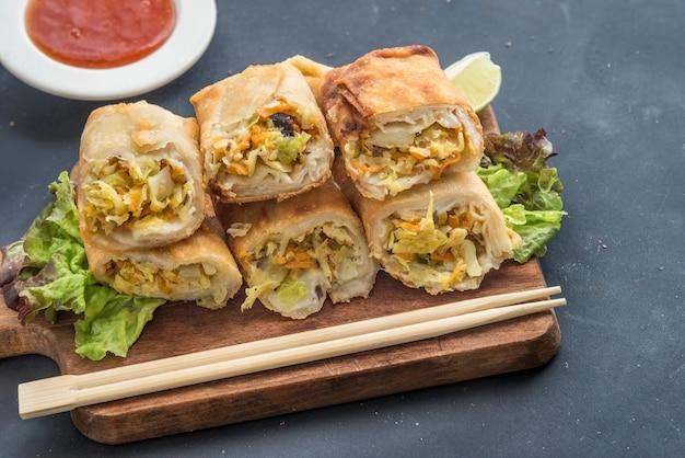 Gebakken groente loempia's met verse ingrediënten geserveerd en zure saus in een oosters restaurant