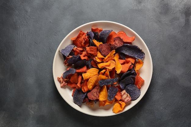 Gebakken groentechips- paarse granaat zoete aardappel, wortel en rode biet.