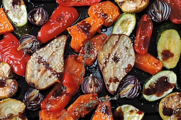 Gebakken groenten en fruit op een bakplaat. veganistisch thema. smakelijk gebakken groenten en fruit met kruiden.