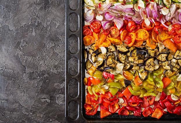Gebakken groenten op een bakplaat. aubergine, courgette, tomaten, paprika en uien. bovenaanzicht