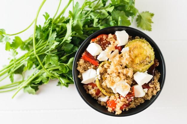 Gebakken groentesalade met quinoa en servische kaas op een witte houten tafel. vegetarisch gerecht. natuurlijk gezond voedsel. bovenaanzicht.