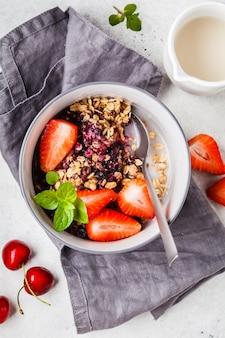 Gebakken havermeel met bessen en melk in een grijze kom, bovenaanzicht. veganistisch ontbijt.