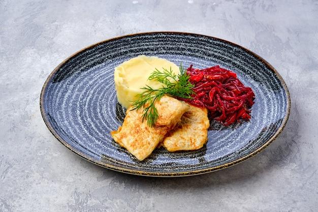 Gebakken heek in paneermeel met aardappelpuree en geroosterde rode biet
