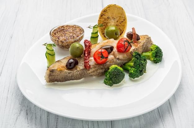 Gebakken heilbot met groenten en mosterd, op het bord